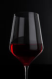 Glass of red wine with reflection on black Royalty Free Stock Photography