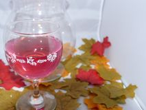 Glass of red wine. A glass of rich red wine,set in front of a candle showing shadows of flickering light set among autumn leaves Stock Photography