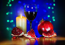 Glass of red wine, ripe pomegranate, and burning candle on the table Stock Photo