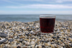 Glass of red wine on the rocky beach. Closeup of glass of red wine on the rocky beach royalty free stock photo