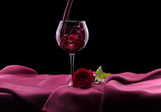 Glass of red wine and rose on black Royalty Free Stock Images