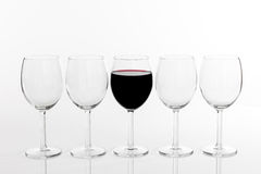 Glass of red wine in a row of empty glasses Royalty Free Stock Images
