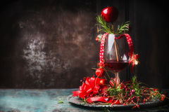 Glass of red wine on rustic table with festive Christmas decoration and rosemary at dark wooden background Royalty Free Stock Photography