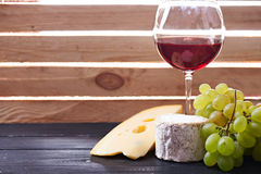 Glass of red wine, served with grapes and cheese Stock Images