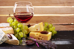 Glass of red wine, served with grapes and cheese Stock Photo