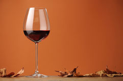 A glass of red wine on a shelf in wood. A glass of red wine in profile, on a shelf in wood, with dry leaves, on a brown background Stock Photo