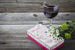 Glass of red wine sitting beside decorative valentine box. Stock Photography