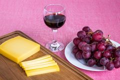 Glass of red wine, sliced yellow cheese Edam on brown wooden cutting board and sweet red grapes on white plate. Still life on a stock images
