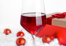 Glass of red wine on snow with christmas balls Stock Photography