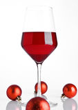 Glass of red wine on snow with christmas balls Stock Images