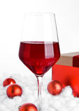 Glass of red wine on snow with christmas balls Royalty Free Stock Photo