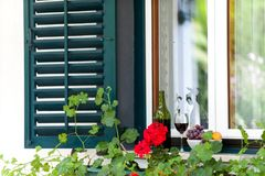 Glass with red wine and some grape on window ledge. Glass and bottle with homemade red wine and some grape on window ledge in garden on a sunny day oute for Stock Photos