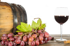 Glass of red wine. With some grapes and oak barrels stock photos