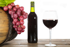 Glass of red wine. With some grapes and oak barrels royalty free stock photography