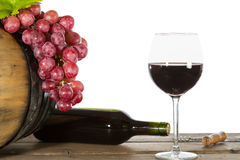Glass of red wine. With some grapes and oak barrels royalty free stock photos
