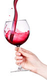 Glass of red wine with splashes in hand isolated Royalty Free Stock Photos