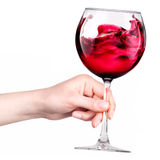 Glass of red wine with splashes in hand isolated Stock Images