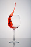 Glass red wine splashing on a white background. Glass of red wine splashing on a white background Stock Photography