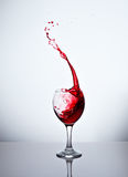 A glass with red wine and sprays. One glass with red wine and sprays Royalty Free Stock Photos
