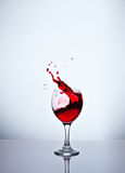 A glass with red wine and sprays. One glass with red wine and sprays Royalty Free Stock Image