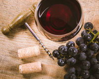 Glass of red wine with a sprig of grapes on a wooden table. Royalty Free Stock Photo