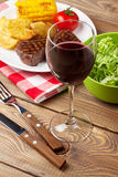 Glass of red wine, steak with grilled potato, corn and salad Stock Photo