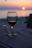 Glass with red wine and Sunset on beach  at the background. summertime vacation concept Royalty Free Stock Image