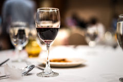 Glass of red wine on the table. Glass of red wine on the table in dark tone Stock Image