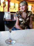 Glass of red wine on the table and a girl Stock Photos