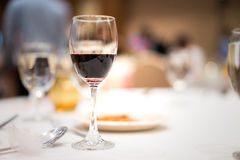 Glass of red wine on the table. Glass of red wine on the table in party Royalty Free Stock Image