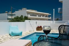 A glass of red wine on the table by the pool stock photography
