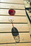 Glass of red wine on the table. Glass of red wine on a sunny day on a wooden table in a backlit Stock Image