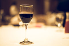 Glass of red wine on the table. Glass of red wine on the table in vintage tone Royalty Free Stock Photo