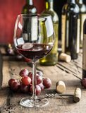 Glass of red wine on the table. Wine bottle and grapes at the ba Stock Image