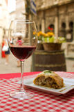 Glass of red wine and a tasty food royalty free stock image