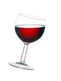 Glass of red wine, tilted, isolated on white background. Backlit glass of real wine at jaunty angle Stock Image