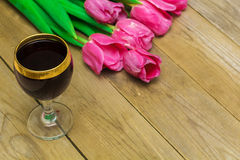 Glass with red wine and tulips Royalty Free Stock Images
