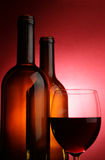 Glass of red wine and two bottles Stock Image
