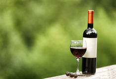 Glass of red wine and unopened bottle outdoors Royalty Free Stock Photos