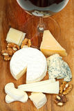 Glass of red wine and various cheeses Stock Images