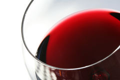 Glass of Red Wine on White. Closeup of a glass of red wine, with white background. Shallow DOF, with focus on front edge of glass stock photography