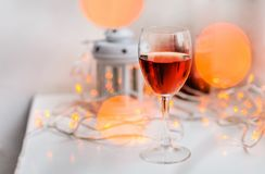 Wine glass on the decorated table and blurred bokeh background. A glass of red wine on the white table with warm bokeh lights big and small. Blurred decorations stock images