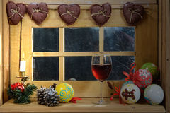 Glass of red wine at the window, with a christmas Royalty Free Stock Image