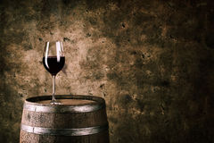 Glass of red wine on wine barrel. Shot with dark background stock images
