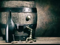 Glass of red wine and wine bottle. Oak wine keg at the backgroun Royalty Free Stock Image