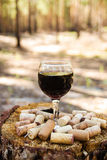 A glass with a red wine and wine corks on a stump on a background of a summer forest. royalty free stock photography