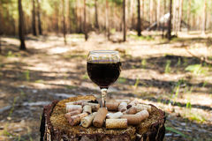 A glass with a red wine and wine corks on a stump on a background of a summer forest. stock photos
