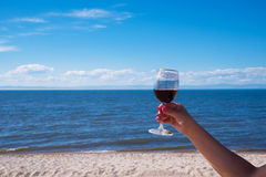 A glass of red wine in a woman`s hand with a beautiful manicure. Against the backdrop of a sunny beach. Blue sea and. A glass of red wine in a beautiful female stock photos
