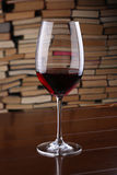 Glass of red wine on wooden table against backdrop the books Royalty Free Stock Photo