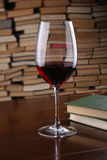 Glass of red wine on wooden table against backdrop the books Stock Photos